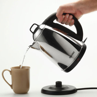 hand pouring hot water from Aroma Electric Kettle into a mug