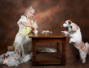 little blonde girl serving tea to her two little dogs