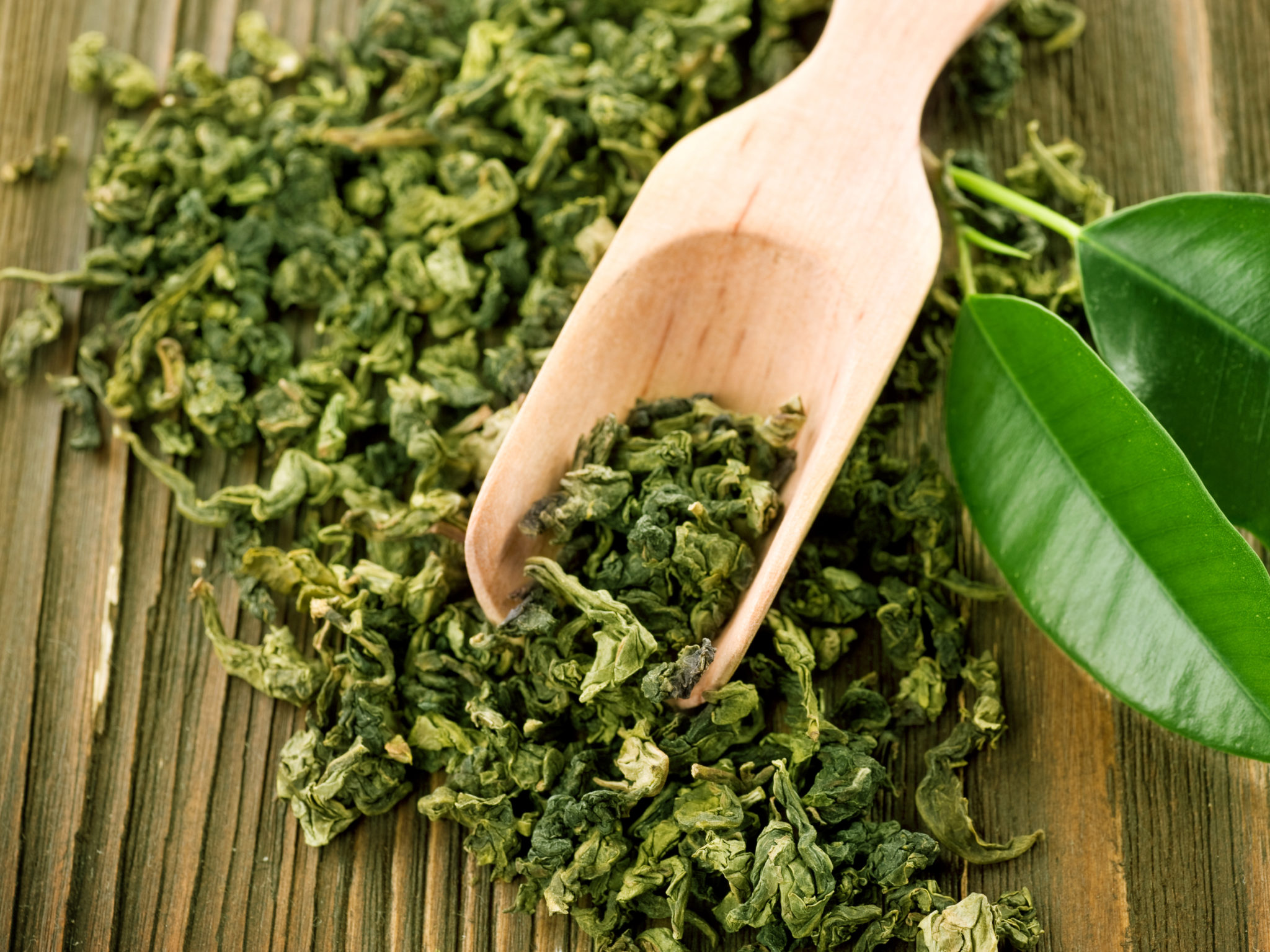 dried loose leaf green tea and plant leaves on a wooden surface with a wooden spoon for scooping