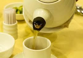 white ceeramic tea pot pouring tea into white cup on yellow tablecloth