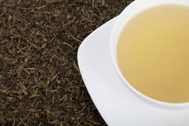 white tea in white tea cup and saucer resting on bed of dried tea leaves